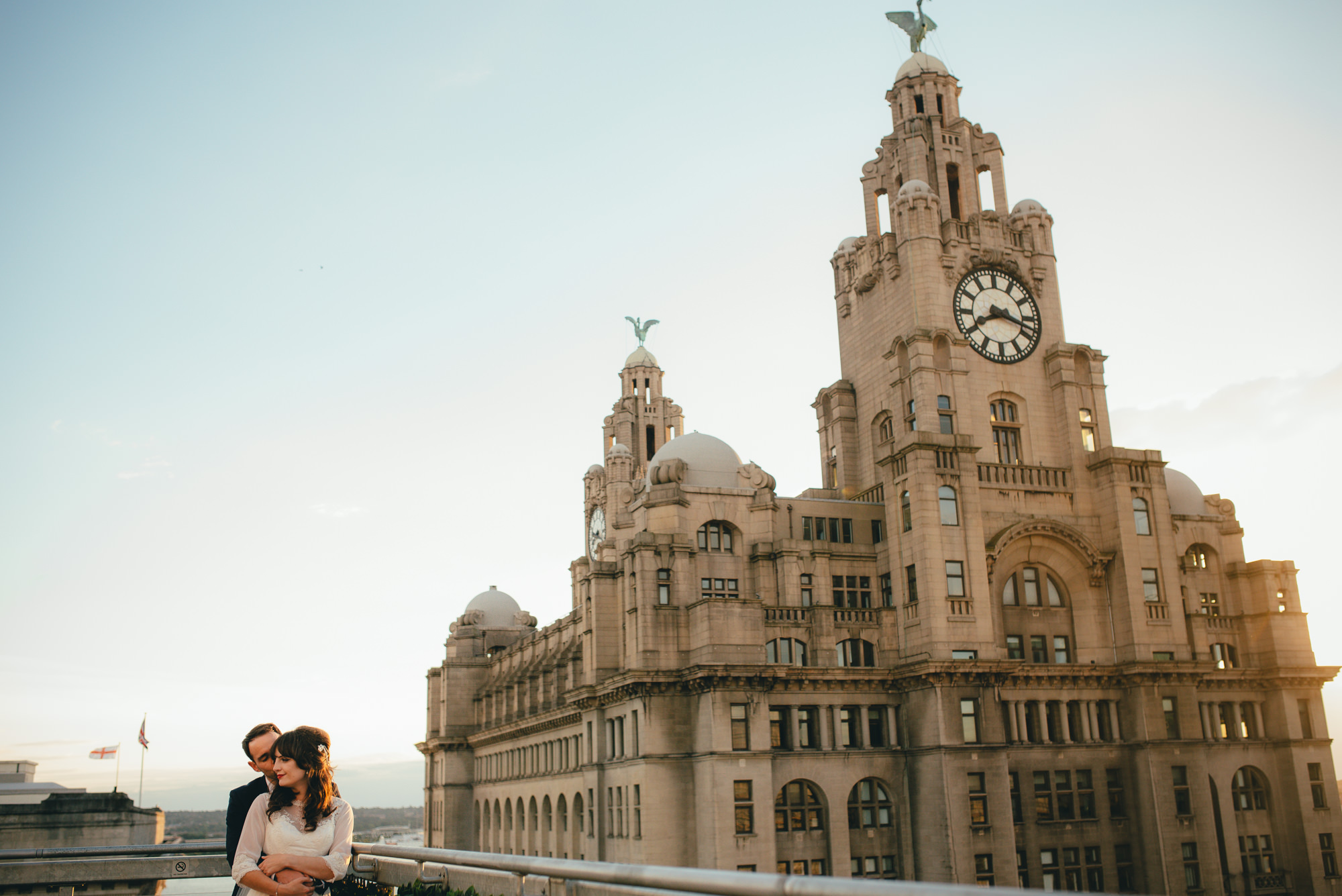 Oh my oh my wedding photography couple on roof by liver building at sunset